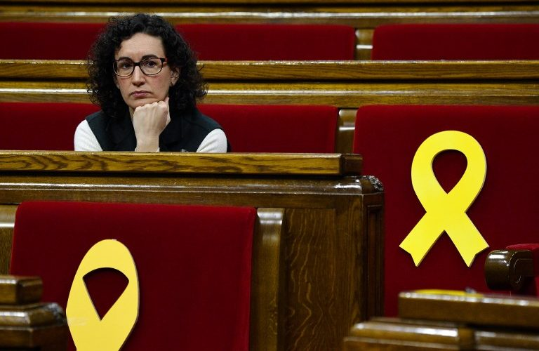 Member of Catalonia's parliament Marta Rovira sits next to yellow ribbons placed on empty seats reserved for the jailed Catalan separatist leaders Oriol Junqueras and Jordi Sanchez at the Catalonia's parliament before a session on March 1, 2018 in Barcelona.   Catalan separatist parties are considering appointing jailed civil society leader Jordi Sanchez as regional president as their negotiations to try and find a suitable candidate draw to a close, a lawmaker said. These parties -- which form an absolute majority in the Catalan parliament -- have been negotiating for weeks over who to pick as candidate for the regional presidency as Catalonia's sacked leader Carles Puigdemont is in self-exile in Belgium.   / AFP PHOTO / LLUIS GENE