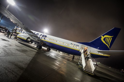 Passengers step down a passenger aircraft of the Irish low-cost airline company Ryanair on the tarmac of the Airport in Frankfurt am main, western Germany on December 21, 2017. Passengers travelling with Ryanair in Germany on December 22, saw little disruption from a four-hour strike called by a pilots' union, with most flights leaving as scheduled, and only some delays. Germany's powerful Cockpit union had asked Ryanair pilots to walk off the job from 5-9am (0400-0800 GMT) in a battle for recognition from the Irish no-frills carrier whose workers have been calling for better pay and conditions across Europe. But the first-ever strike action by Ryanair pilots in the company's 32-year history appeared to have made little impact, with no cancellations reported.   / AFP PHOTO / dpa / Frank Rumpenhorst / Germany OUT