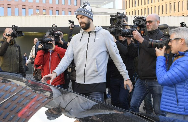 Journalists gather around Barcelona's Spanish defender Gerard Pique (C) as he leaves after appearing in court for driving without a valid licence in Barcelona on November 26, 2018. (Photo by LLUIS GENE / AFP)
