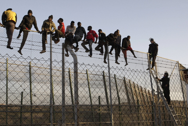 GRA030 MELILLA, 22/10/2014.- Agentes de Policía junto a algunos de los ochenta inmigrantes que están encaramados desde primera hora a la valla de Melilla, fronteriza con Marruecos, tras el último intento de entrar en la ciudad autonóma protagonizado por varios centenares de subsaharianos, algunos de los cuales, al menos una docena, ha conseguido superar el vallado perimetral. EFE/Francisco G. Guerrero