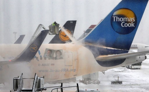 An airport employee uses a de-icing engine to defrost a Thomas Cook airplane on the snow covered ground of the airport in Frankfurt am Main, western Germany, on March 12, 2013 as the Europe's third-busiest hub was able to re-open one runway for takeoffs only on the afternoon, after being forced to close completely due to heavy snow..  AFP PHOTO / DANIEL ROLAND (Photo by DANIEL ROLAND / AFP)