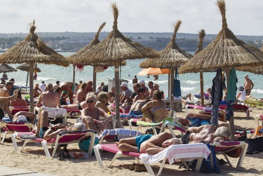 Tourists enjoy a sunny day at the Playa de Palma beach in Palma de Mallorca on September 24, 2019. - Britain has repatriated ten percent of nationals who were stranded abroad after the collapse of travel firm Thomas Cook, as anger erupted over excessive management pay. (Photo by JAIME REINA / AFP)
