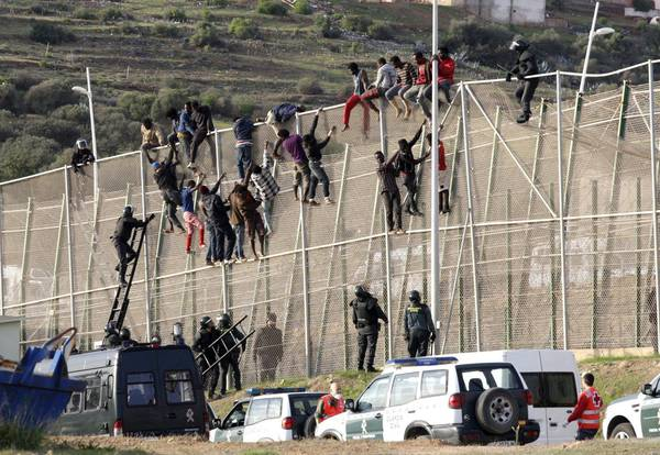 epa04447577 Sub-Saharan migrants try to climb up a border fence in another mass attempt to jump into Melilla, the Spanish exclave in northern Africa, 15 October 2014. About 200 immigrants tried to reach Melilla, the second such attempt in the past 24 hours.  EPA/F.G. GUERRERO