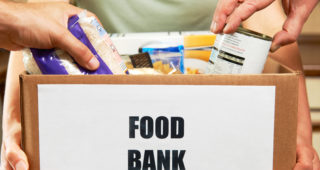Close Up Of people Making Donations To Food Bank