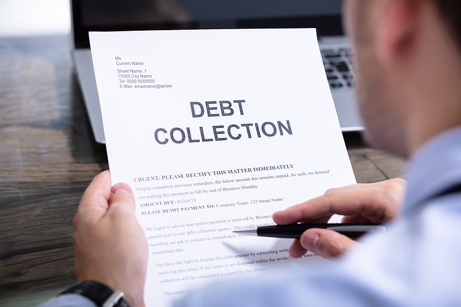 Man Reading Debt Collection Notice Letter At Desk